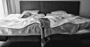 Two adjacent beds in black and white with different light strength. The left one is bright, the right side is dim. Concepts of differentiation, discrimination royalty free stock image