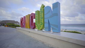 Left pan of the Cancun sign on the beach