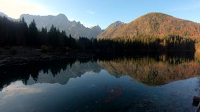 Left pan at Laghi di Fusine lake with reflection of Alps mountains on calm water stock video
