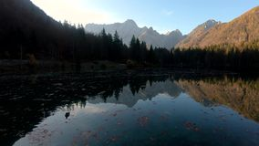 Left pan at Laghi di Fusine lake with reflection of Alps mountains on calm water stock footage