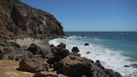Left pan to secluded beach at Point Dume. Scene from Point Dume, a promontory on the coast of Malibu, California that juts out into the Pacific Ocean. The point stock video