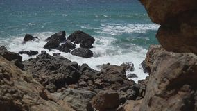 Left pan to waves at Point Dume. Scene from Point Dume, a promontory on the coast of Malibu, California that juts out into the Pacific Ocean. The point, a long stock footage