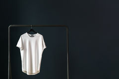 In the left part of image white empty T-shirt with short sleeves on a hanger. Stock Photo
