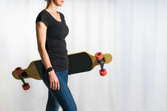 In the left part of the image a young woman dressed in a black T-shirt and jeans standing and holding a longboard. Stock Photography