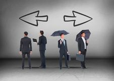 Left and right arrows and Group of Businessmen with umbrellas looking in opposite directions Stock Image