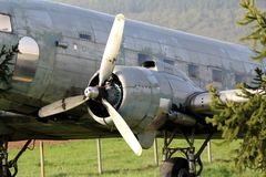 Left rotary engine of Douglas Dakota DC-3 WWII plane placed in field at exhibit surrounded with uncut grass and trees. On warm sunny spring day royalty free stock images
