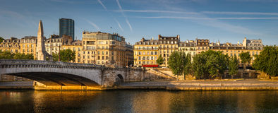 Left Seine river bank bathed in the early morning summer light Stock Image