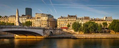 Left Seine river bank bathed in the early morning summer light. Paris buildings along the River Seine, Tournelle bridge (pont de la Tournelle) and its statue of Stock Image