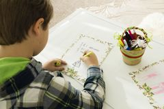 A boy drawing on a paper. On the left side of the image is a boy at the white table is drawing on the paper. the image shows a part of his  back and his head. he Stock Photo