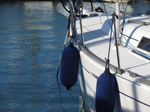 Left side of white sailing boat with two blue fenders.  Royalty Free Stock Photo