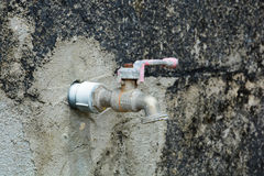 Left to age. A water tap long been used as it shows signs of age and non usage with visible rust and weathering and spider web. grunge wall behind it Royalty Free Stock Photo