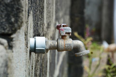 Left to age. A water tap long been used as it shows signs of age and non usage with visible rust and weathering and spider web. grunge wall behind it Stock Image