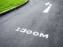 Left turn arrow signals a marked run path 1,300 meters. Royalty Free Stock Photography