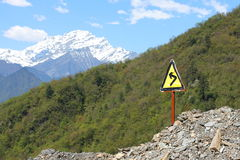 Left turning sign before snow mountain Royalty Free Stock Photo