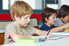 Lefthanded boy in elementary school. Writing with a pencil Stock Image