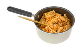 Leftover pasta with tomato sauce in pan with spoon Stock Photo
