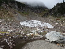 A leftover snowfield in a valley Stock Photo