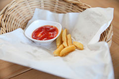 Leftover traditional French fries with ketchup in bambom basket Stock Photos
