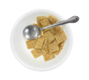 Leftover whole wheat cereal in bowl with spoon Stock Image