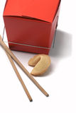 Leftovers. In a red to go box focused on fortune cookie with chopsticks on white background Stock Image