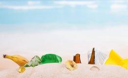 Leftovers, banana skins, plastic, glass bottles in  sand against  sea. Stock Images