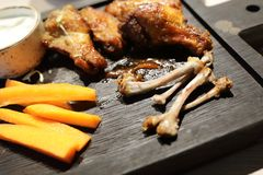 Leftovers of chicken wings. On wooden board royalty free stock image