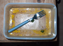 Leftovers eaten and dirty tupperware and fork empty unclean Stock Photos