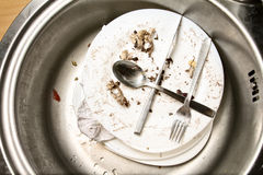 Leftovers in a sink. Dirty dishes and bits of food in the kitchen Stock Photography
