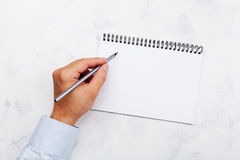 Leftyen skriver i tom anteckningsbok på den vita bästa sikten för tabellen Internationell Lefthandersdag Royaltyfri Bild