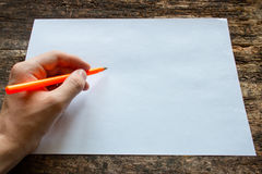 Leftyen skriver med en kulspetspenna på ett ark av papper på trätabellen Royaltyfri Fotografi