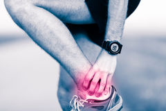 Leg ankle pain, man holding sore and painful foot Stock Photo