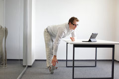 Leg - arm exercise during office work Stock Photos