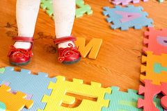 Leg of baby on the floor with puzzles Stock Image