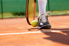 Leg with ball and tennis racket. Sportsman catches up his tennis ball with racket Stock Photos