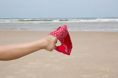 Leg on Beach holding bikini on summer Stock Image