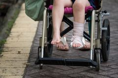 Leg broken child on wheelchair walked in park. Patient boy sitting on wheelchair to give a walk and refreshment in park. Broken leg by accident wrapped with stock photo