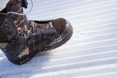 Leg in a brown boot stepping on track cleared of snow. Royalty Free Stock Photography