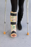 Leg cast and crutches. Broken leg in cast with autographs and crutches Royalty Free Stock Image