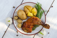 Leg of chicken served with potatoes in jackets royalty free stock photos