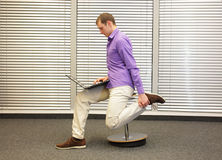 Leg exercise during office work. Man sitting on pneumatic stool, working with laptop in his office royalty free stock images