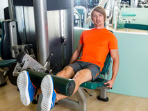 Leg extension exercise man at gym workout Royalty Free Stock Images