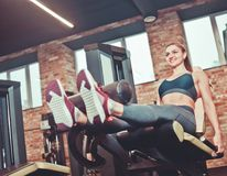 Leg extension exercise workout smilling sporty woman. Indoor at gym royalty free stock photography