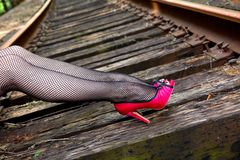 Leg fashion. Female legs in fishnet stockings and hot pink high heels posing on railroad tracks. Shallow depth of field, focus point on immediate foreground Royalty Free Stock Images