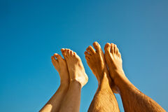 Leg and feet of a man and a child with clear blue Royalty Free Stock Images