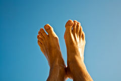 Leg and feet of a man with clear blue sky Stock Images