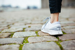 Leg of female jogger walking on pavement Royalty Free Stock Images