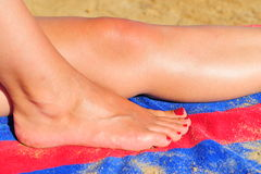 Leg and foot of woman on beach Stock Image