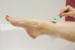 The leg of a girl in the bathroom during the spa procedures, which holds suds depilation using female razor Royalty Free Stock Images