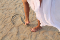 Leg girl draws in the sand heart Royalty Free Stock Photo