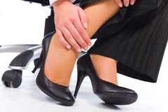 Leg Hurt. Massaging tired hurt leg due to wearing all day high heels royalty free stock images